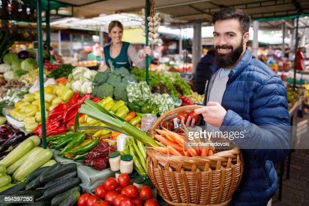 Young man buying vegetables at farmer's market stall.