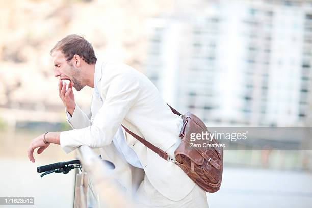 Young man by railings yawning