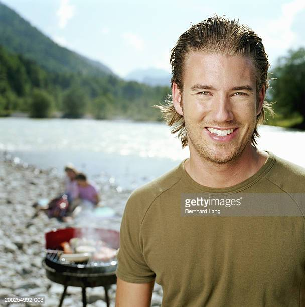 young man by river, portrait, barbecue in background - flussufer stock-fotos und bilder