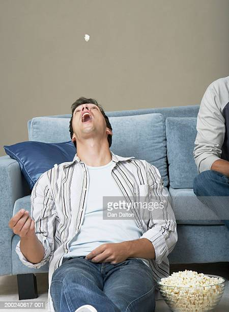 Young man by sofa, tossing popcorn in air, head back and mouth open