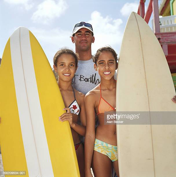 young man by two girls (10-12) holding surfboards, smiling, portrait - 10 11 years stock photos and pictures