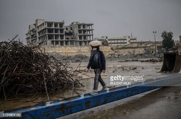 Young man carries a bag of bread on his head as he walks along a metalic beam in the northern Syrian city of Raqa on February 14, 2019. - In 2014,...