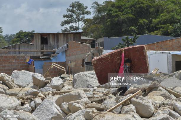 TOPSHOT A young man carries a mattress amid the rubble left by mudslides caused by heavy rains in Mocoa Putumayo department southern Colombia on...