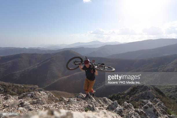 Young man carries bike up high mountain ridge