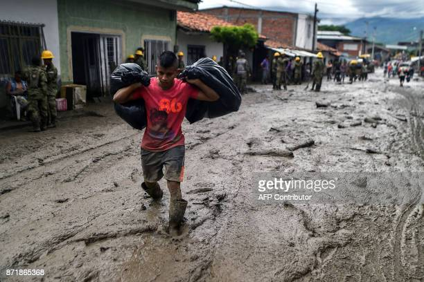 A young man carries his belongings across a muddy street after a mudslide due to heavy rains affected Corinto in Cauca department southwest Colombia...