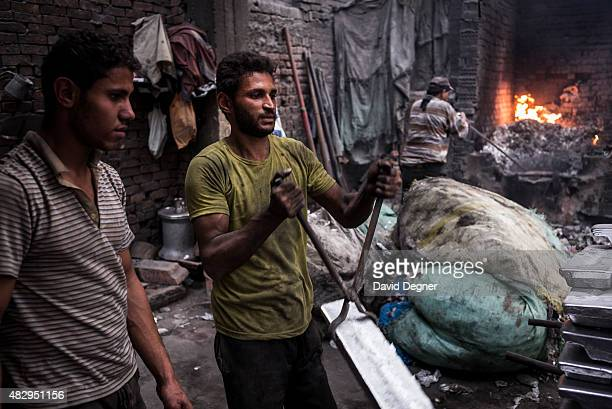A young man carries the final pure ingots of aluminum for reuse on December 18 2014 in Cairo Egypt Nestled under the cliff of Mokattam is Manshiyat...
