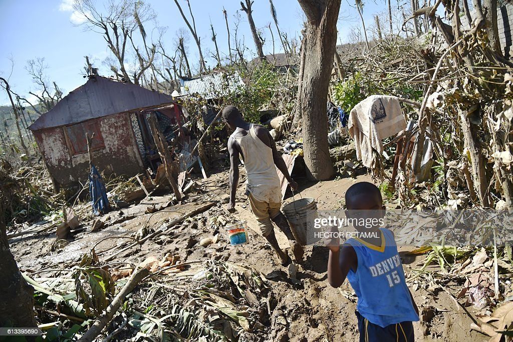 A young man carries water to remove the mud of his house destroyed by Hurricane Matthew in Jeremie, Haiti, on October 8, 2016. The full scale of the devastation in hurricane-hit rural Haiti became clear as the death toll surged over 400, three days after Hurricane Matthew leveled huge swaths of the country's south. / AFP / HECTOR