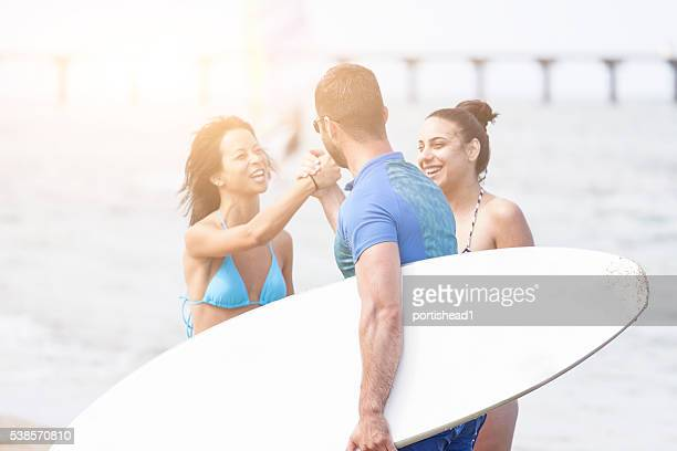 Young man carring a surfboard greeting his friends