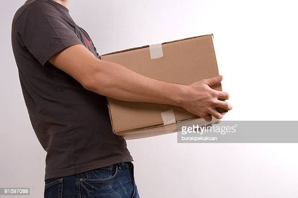 young man carrying a box - chubby credit stock pictures, royalty-free photos & images