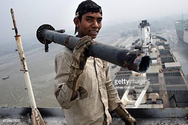 A young man carrying a metal pole that he has scavenged from a mega freighter that has been left to be disassembled on Chittagong beach Where do the...