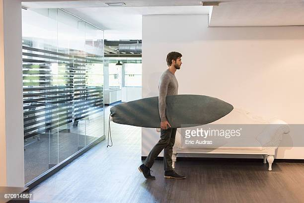 Young man carrying a surfboard at home