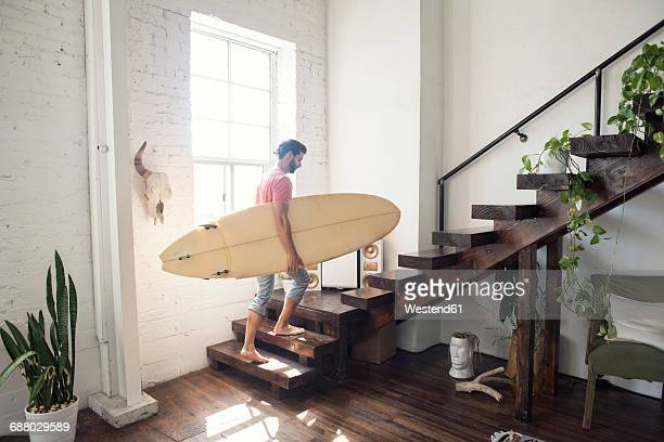 Young man carrying a surfboard on stairs in a loft