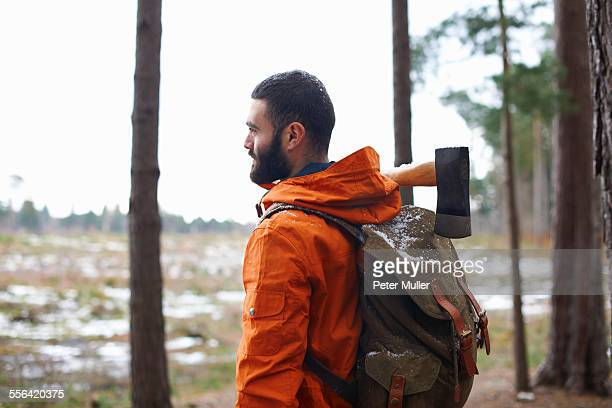 Young man carrying axe looking out from forest