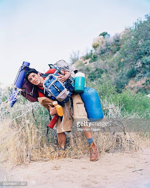 Young man carrying backpack and camping gear outdoors