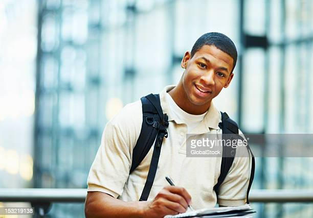 Young man carrying bag and writing on book