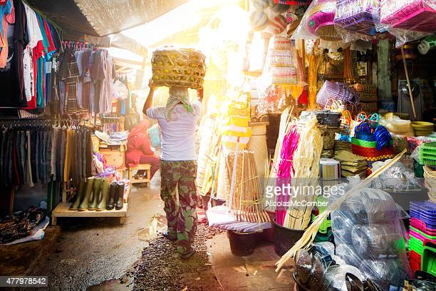 young man carrying basket of oranges on head through market - balinese culture stock pictures, royalty-free photos & images