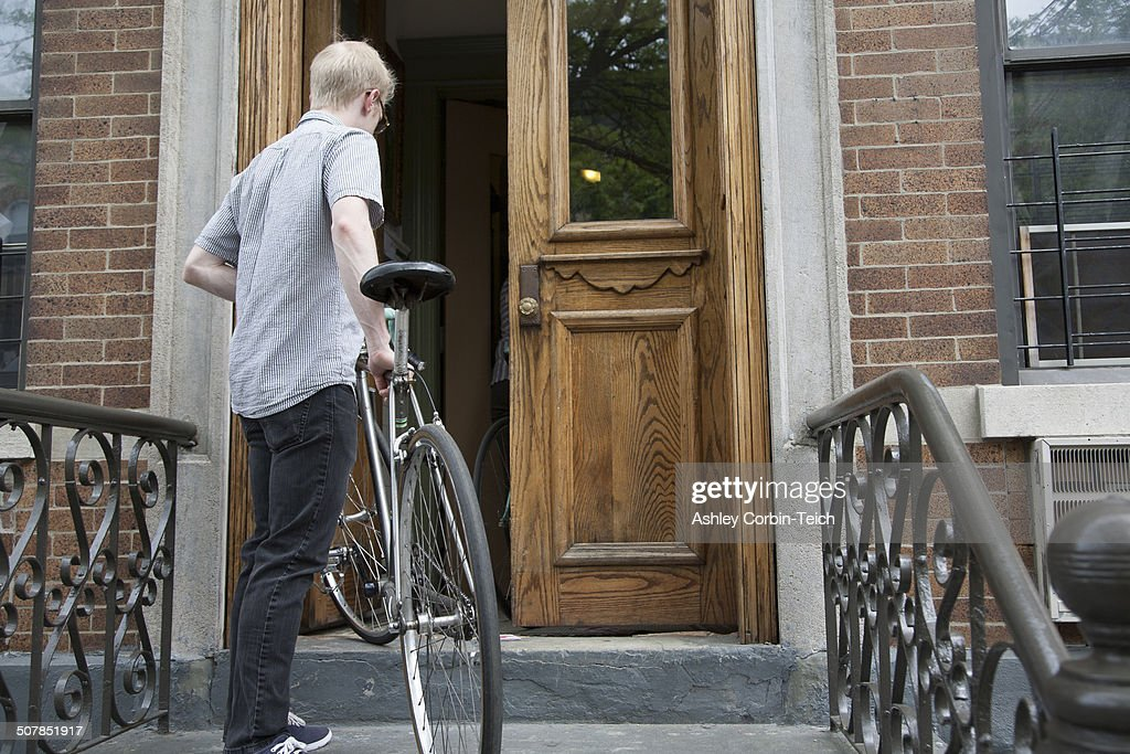 Young Man Carrying Bicycle Up Steps To Front Door Stock Photo