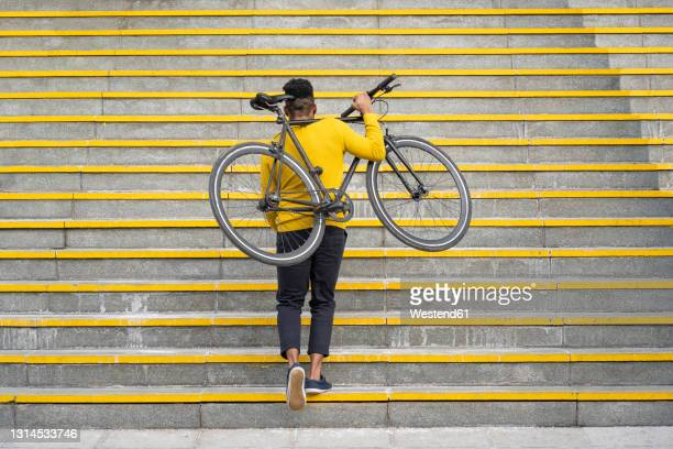 young man carrying bicycle while climbing on staircase - staircase stock pictures, royalty-free photos & images