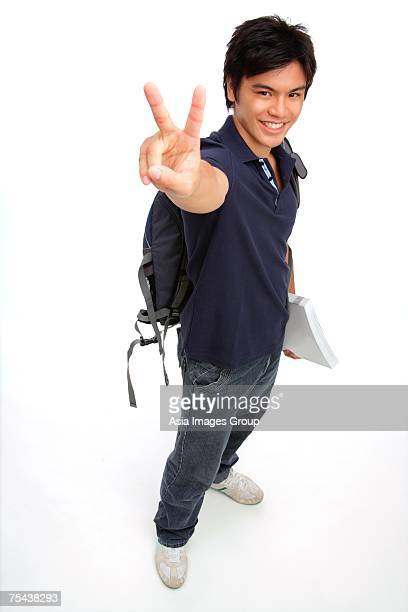 Young man carrying books and a backpack, making peace sign