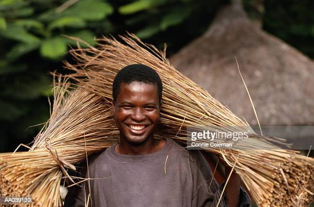 Young man carrying bundles of straw, smiling, portrait