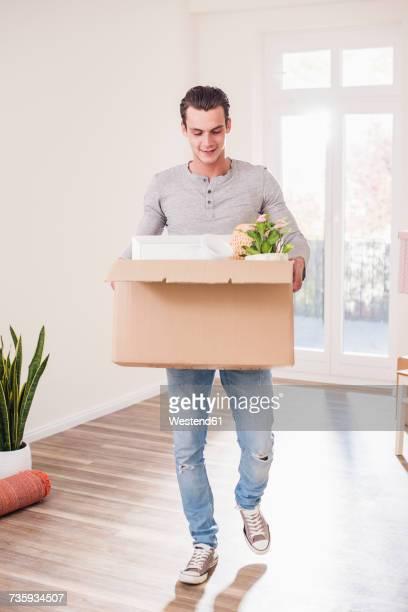 young man carrying cardboard box in new home - carrying fotografías e imágenes de stock