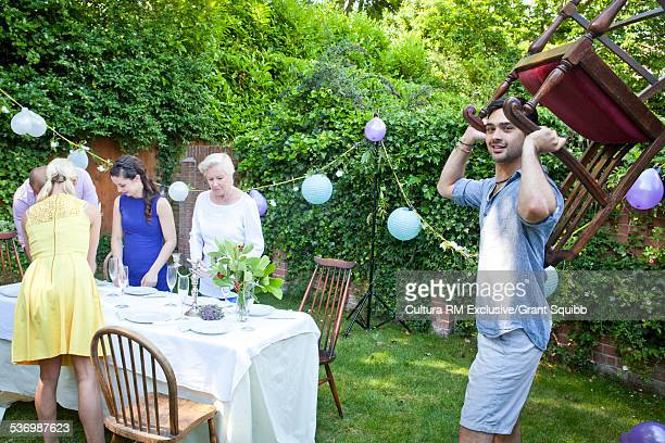 Young man carrying chair for garden party table
