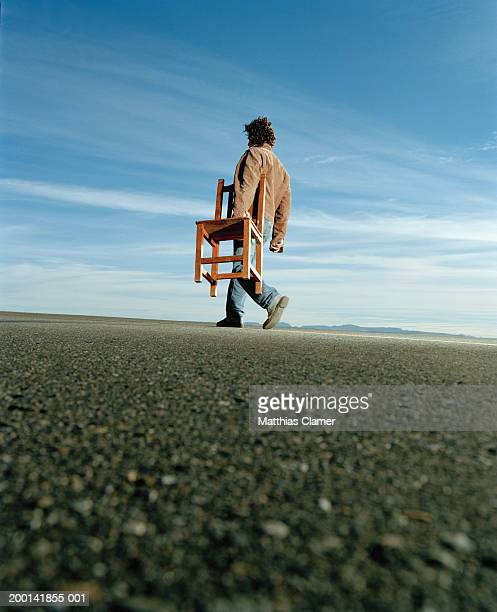 Young man carrying chair outdoors, side view, low angle view
