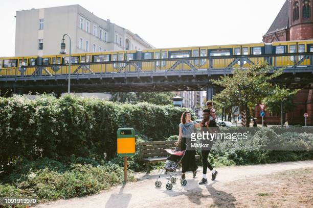 young man carrying daughter on shoulders while woman pushing baby stroller at footpath against railway bridge - berlin stock-fotos und bilder