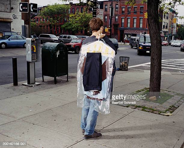 Young man carrying dry cleaning on street, rear view