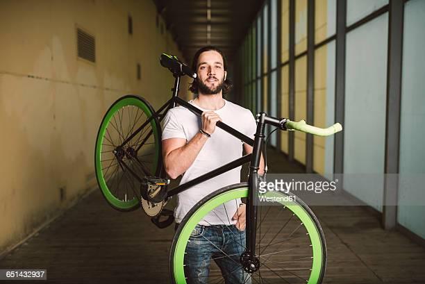 Young man carrying fixie bike