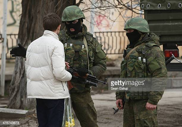 Young man carrying flowers confronts heavily-armed soldiers displaying no identifying insignia in a street in the city center on March 1, 2014 in...