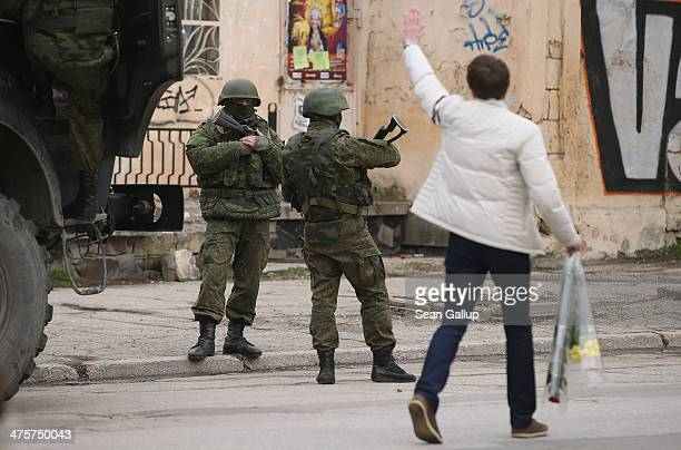 A young man carrying flowers who moments before had confronted heavilyarmed soldiers displaying no identifying insignia waved goodbye to them in a...