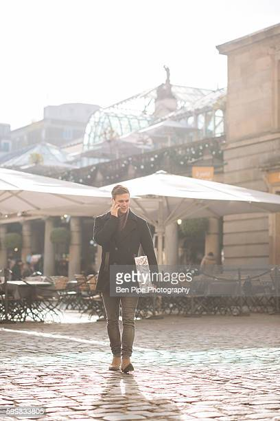 Young man carrying gift and chatting on smartphone in Covent Garden, London, UK