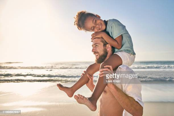 young man carrying girl on shoulder on beach - female hairy chest stock pictures, royalty-free photos & images