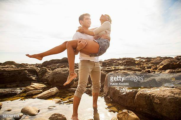 Young man carrying girlfriend across rock pool on beach