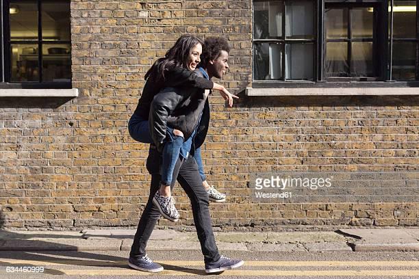 Young man carrying girlfriend piggyback at brick building