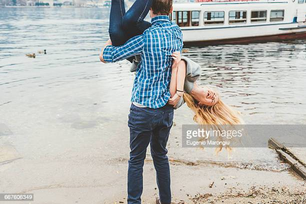 young man carrying girlfriend upside down on lakeside, lake como, italy - exhilaration stock photos and pictures