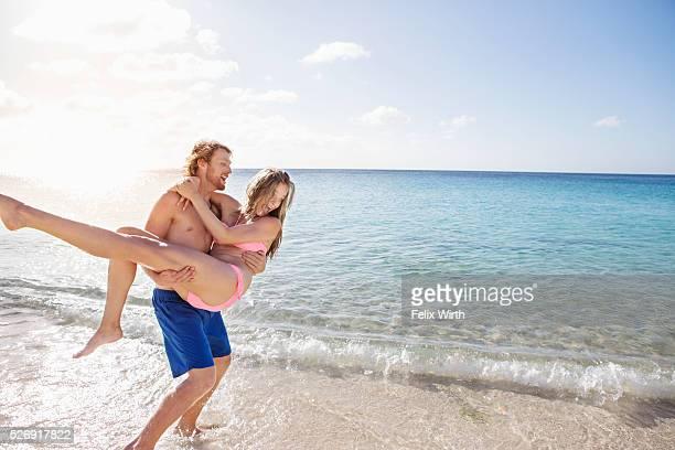 Young man carrying his girlfriend along sandy beach