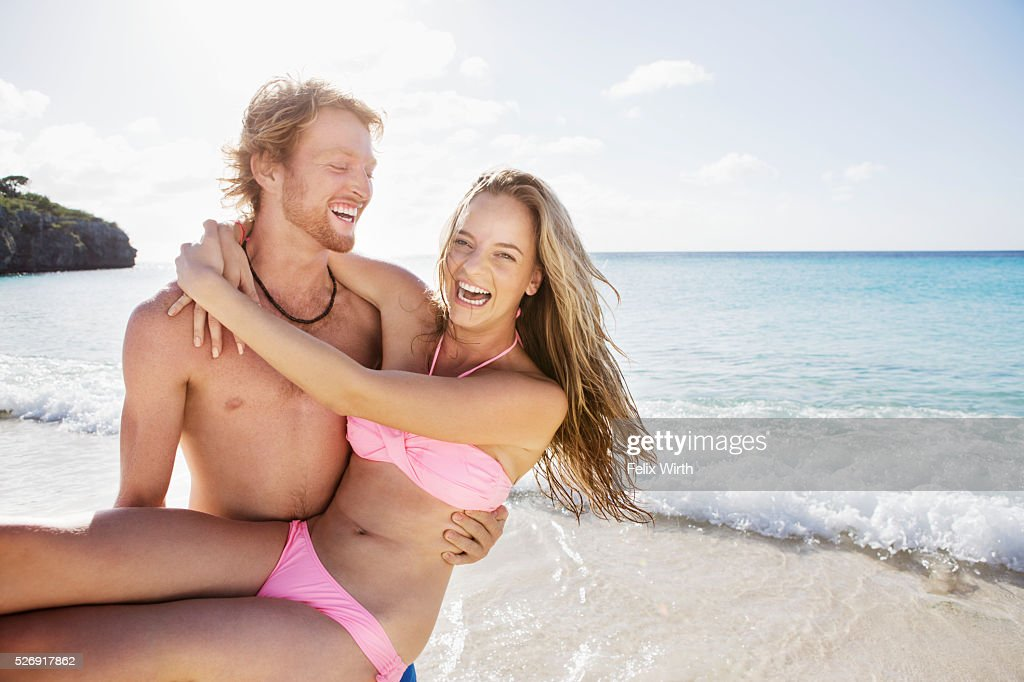 Young man carrying his girlfriend along sandy beach : Stockfoto