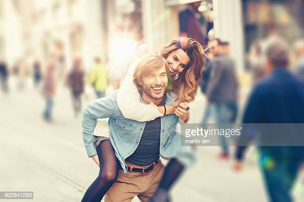 young man carrying his girlfriend at piggyback - love at first sight stock pictures, royalty-free photos & images