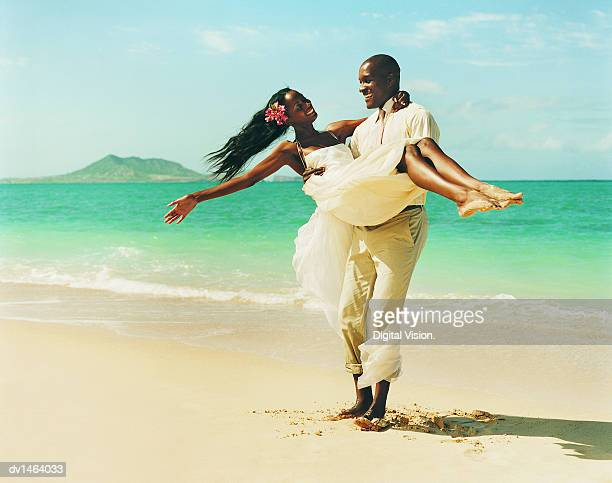 Young Man Carrying his New Bride in the Sand at the Waters Edge