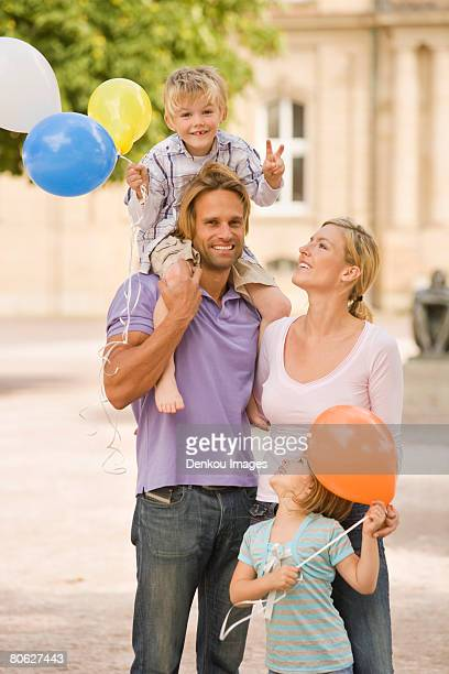 Young man carrying his son on his shoulders and his wife and daughter looking at him