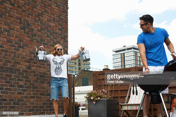 Young man carrying ice buckets at rooftop barbecue