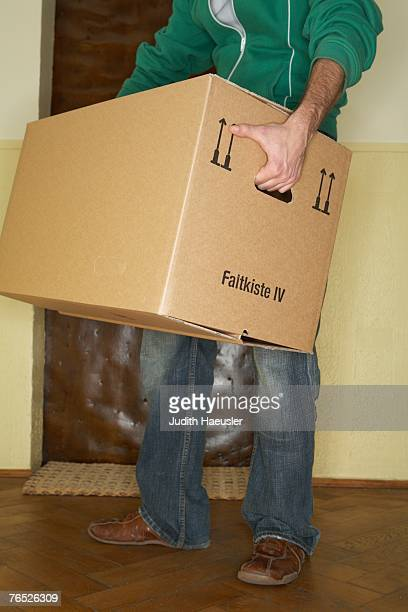 Young man carrying large cardboard box, low section