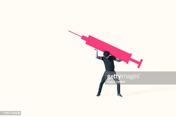 young man carrying large pink injection - oresund region stock pictures, royalty-free photos & images