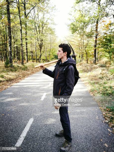 Young Man Carrying Mattock While Standing On Road In Forest