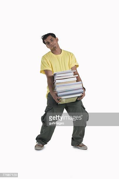 young man carrying pile of books, portrait - man holding book stock pictures, royalty-free photos & images