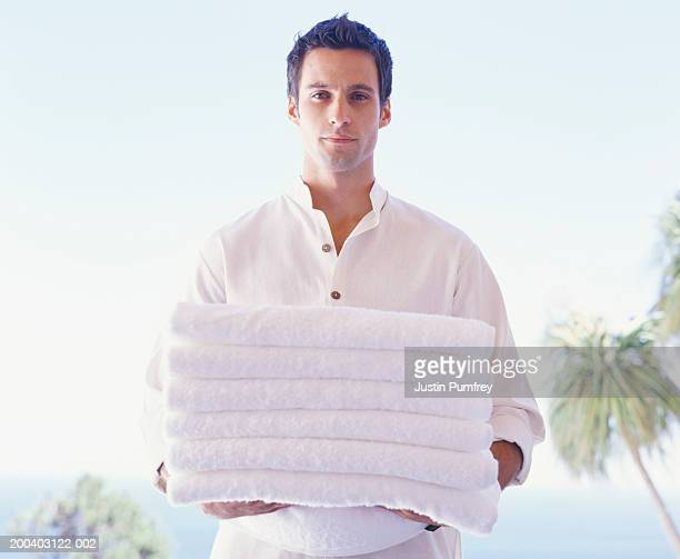 young man carrying pile of folded clean towels, portrait - オープンネック ストックフォトと画像