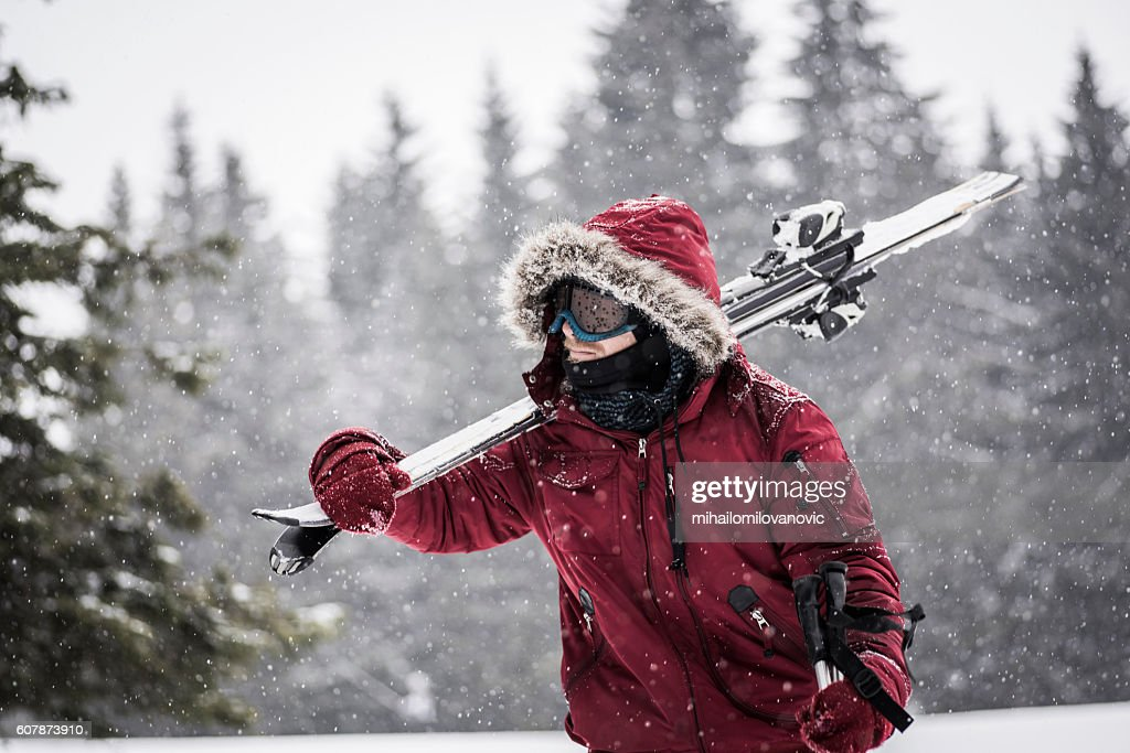 Young man carrying skis through snowy forest : Stock Photo