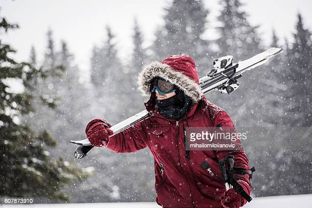 Young man carrying skis through snowy forest
